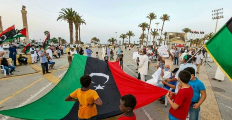 People gather with Libyan national flags at the Martyrs' Square in the centre of Tripoli on August 20, to mark the 10th anniversary of the city's capture from the forces of former leader Moamer Kadhafi.  By Mahmud TURKIA (AFP/File)