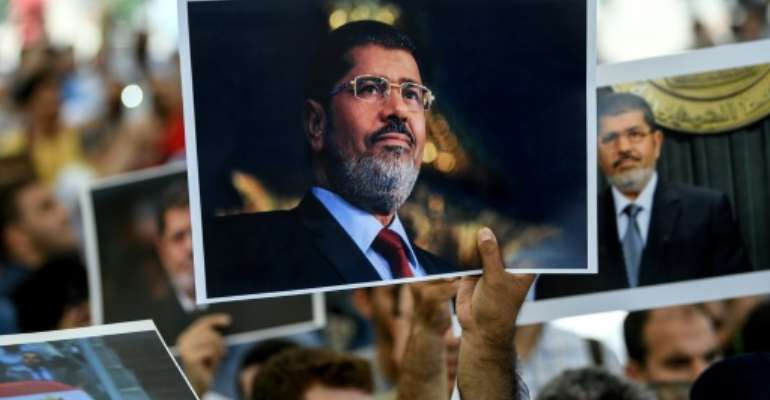 People hold picture of Egyptian President Mohamed Morsi during a symbolic funeral cerenomy on June 18, 2019 at Fatih mosque in Istanbul.  By  (AFP/File)
