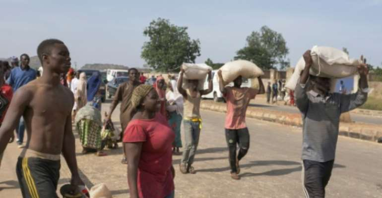 People in Nigerian city Jos carried off bags of food on their heads during a mass looting of a warehouse.  By Ifiok Ettang (AFP)