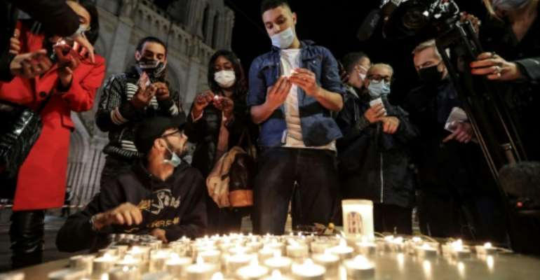People lights candle outside the Notre-Dame de l'Assomption Basilica in Nice in tribute to the three victims of a knife rampage, which France's president called an 'Islamist terrorist attack'.  By Valery HACHE (AFP)