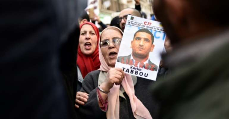 People march with signs calling for the release of detained Algerian opposition figure Karim Tabbou on January 24, 2020, during the 49th consecutive Friday demonstration against the Algerian government and the ruling class in Algiers.  By RYAD KRAMDI (AFP/File)