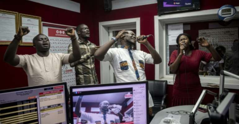 People pray and sing during a worship radio show at Accra FM station in Accra.  By CRISTINA ALDEHUELA (AFP/File)