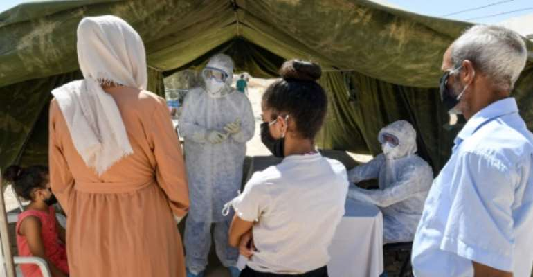 People queue to get tested for coronavirus at the field hospital in El Hamma. The town's hospital has no intensive care beds, and the army set up the field hospital in mid-August to bolster the local response and screen suspected cases.  By FETHI BELAID (AFP)