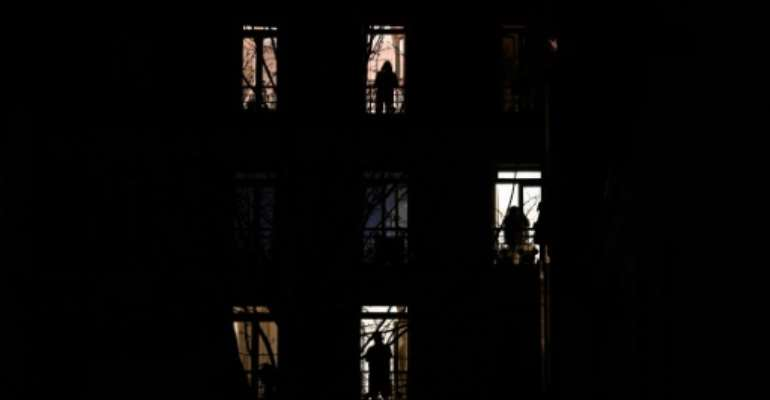 People stand by their windows and applause in solidarity with healthcare workers on the frontline of the coronavirus outbreak in Paris in March.  By PHILIPPE LOPEZ (AFP/File)