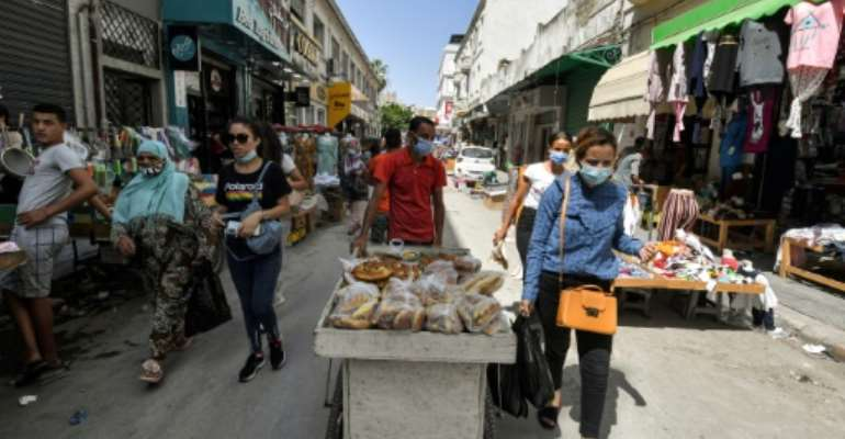 People walk along an alley in Tunisia's capital Tunis on July 28, 2021.  By FETHI BELAID (AFP/File)