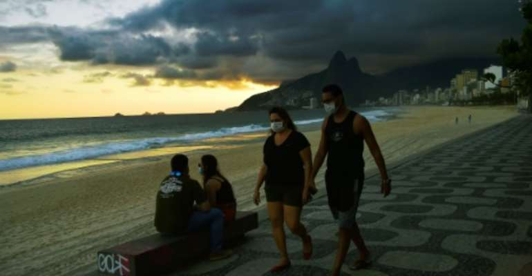 People wear face masks onIpanema Beach in Rio de Janeiro on May 19, 2020, as Brazil recorded its highest yet daily death toll from COVID-19.  By Carl DE SOUZA (AFP)