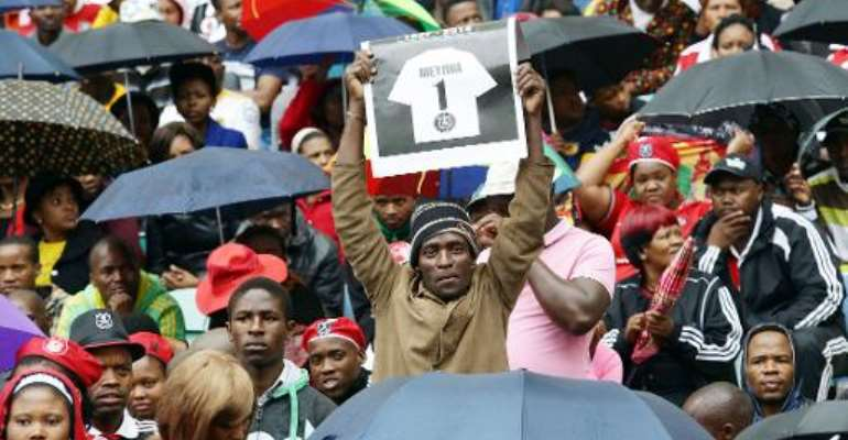 A fan gestures as thousands of South Africans brave the rain and cold weather to gather at the Moses Mabhida stadium to pay their final respects to the late Senzo Meyiwa, during his funeral in Durban on November 1, 2014.  By Rajesh Jantilal (AFP/File)