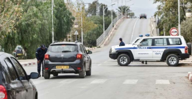Police cars block access to a road near a courthouse in the Algerian city of Blida where an appeal hearing is underway in the trial of the brother of former president Abdelaziz Bouteflika and three other key figures.  By RYAD KRAMDI (AFP)
