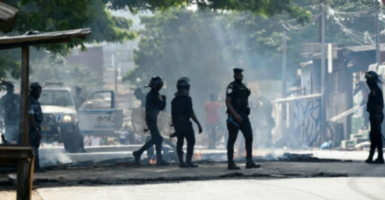 Police clear debris that was placed in the road by young demonstrators during protests against President Alassane Ouattara's run for a third term, in the Yopougon neighbourhood of Abidjan on August 13, 2020.  By SIA KAMBOU (AFP/File)