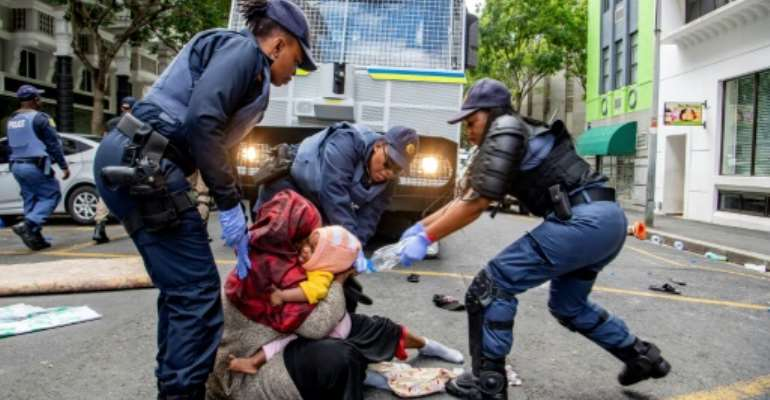 Police fired water guns and stun grenades to disperse the asylum-seekers staging a sit-in protest in the UN's Cape Town office.  By - (AFP)