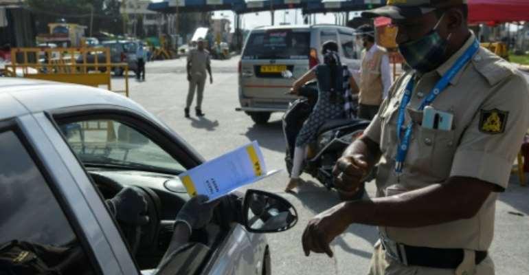 Police stop people travelling to Bangalore and direct them to undergo coronavirus screening.  By Manjunath Kiran (AFP)