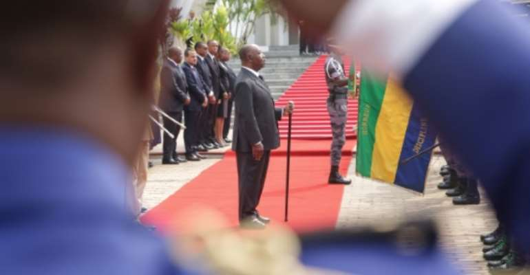 President Ali Bongo, pictured here at a wreath-laying ceremony in August, has been in power for 10 years, succeeding his father Omar. Speculation about his health has swirled since he suffered a stroke in October 2018.  By STEVE JORDAN (AFP)