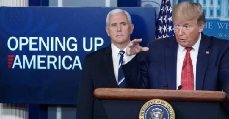 President Donald Trump, flanked by Vice President Mike Pence, announces a gradual reopening of the United States.  By MANDEL NGAN (AFP)