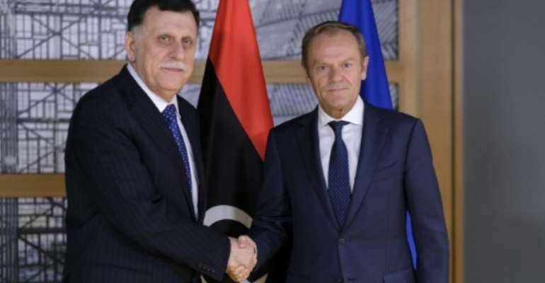 President of the European Council, Donald Tusk (R) welcomes Libyan Prime Minister Fayez al-Sarraj prior to a meeting in Brussels on May 13, 2019. Libyan strongman Khalifa Haftar's offensive against Tripoli represents a threat to international peace, the EU warned.  By OLIVIER HOSLET (POOL/AFP)
