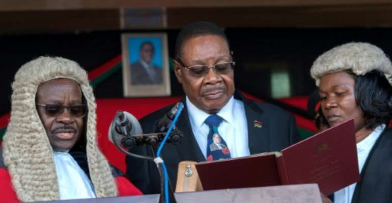 President Peter Mutharika (shown being sworn in May 28, 2019 by Chief Justice Andrew Nyirenda, L) is appealing after the Constitutional Court annulled the election and ordered a re-run, citing 'grave' and 'widespread' irregularities.  By AMOS GUMULIRA (AFP/File)