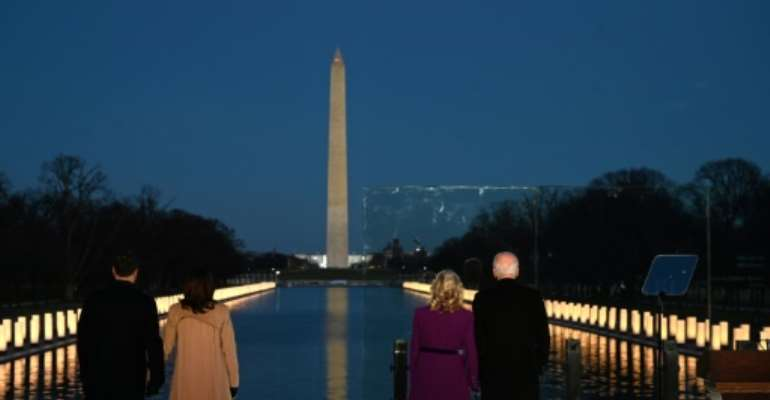 President-elect Joe Biden (R) and incoming First Lady Jill Biden watch as a Covid-19 memorial is lit in Washington, DC.  By Jim WATSON (AFP)