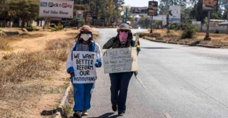 Protest: Zimbabwean novelist Tsitsi Dangarembga, left, and friend Julie Barnes, shortly before their arrest.  By ZINYANGE AUNTONY (AFP)