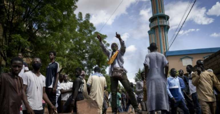 Protesters at a barricade erected in front of the Salam Mosque in Bamako, where Imam Mahmoud Dicko, a leader of the anti-government movement, led prayers on Sunday for victims of the clashes.  By MICHELE CATTANI (AFP)