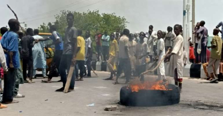 Protesters block a main road in the northern Nigerian city of Maiduguri, demanding the authorities ban a local anti-Boko Haram militia they say is abusing them.  By Audu MARTE (AFP)