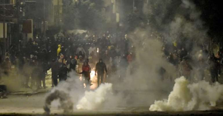 Protesters clash with security forces in the Ettadhamen  suburb of Tunis on Monday night.  By FETHI BELAID (AFP)
