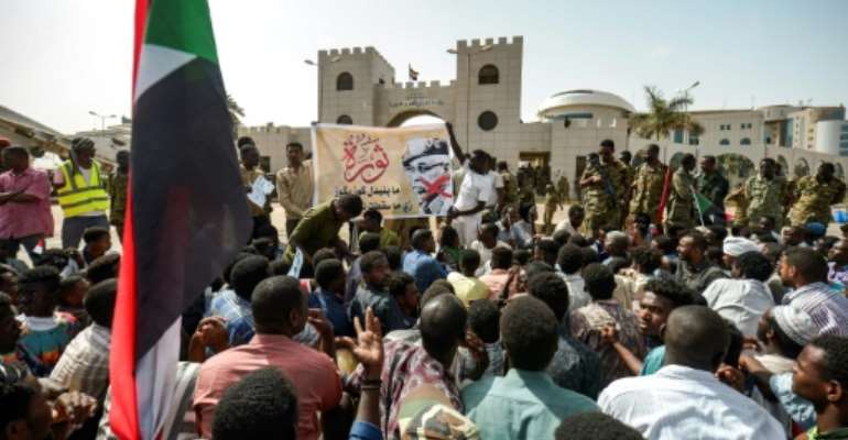 Protesters gather in front of soldiers during a rally demanding a civilian body to lead the transition to democracy, outside the army headquarters in the Sudanese capital Khartoum on April 12, 2019.  By MOHAMMED HEMMEAIDA (AFP)