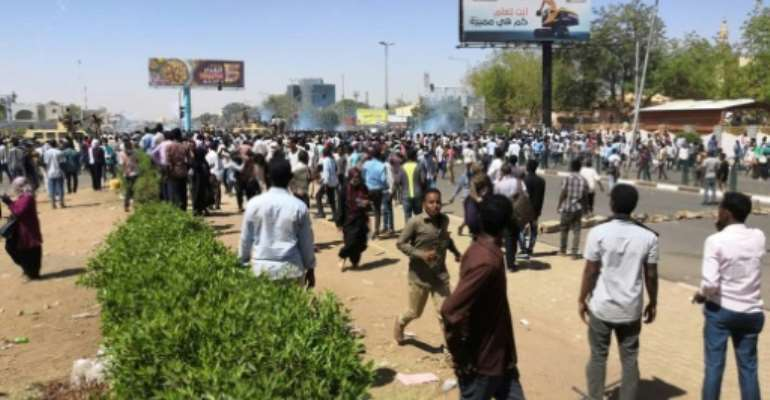 Protesters run for cover from teargas outside the military headquarters in Sudan's capital Khartoum on April 7, 2019.  By - (AFP)