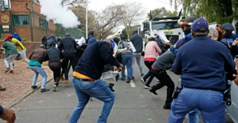 Protesters run from a stun grenade fired by police outside the Zimbabwean Embassy in South Africa's Pretoria.  By Phill Magakoe (AFP)
