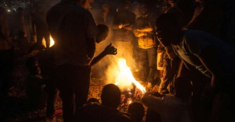 Protesters stand around a fire at a vigil against the result of the May 21 presidential vote in Lilongwe on July 4, 2019.  Malawi's re-elected President Peter Mutharika has condemned the protests.  By AMOS GUMULIRA (AFP)