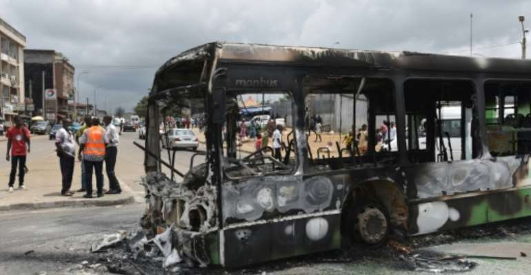 Protesters torched a bus in a working-class district of Abidjan.  By SIA KAMBOU (AFP)
