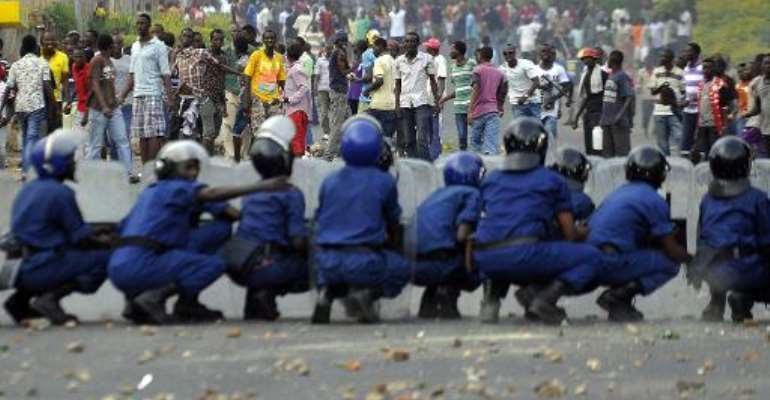 Burundian riot police form a barricade to hold protesters back during a demonstration against the president's bid to cling to power for a third term in Musaga, outskirts of Bujumbura, on April 28, 2015.  By Simon Maina (AFP)