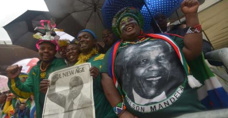 People hold portraits of Nelson Mandela during the memorial service of the South African former president at the FNB Stadium in Johannesburg on December 10, 2013.  By Alexander Joe (AFP)