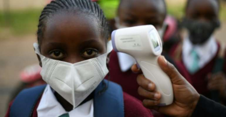 Pupils at Our Lady of Mercy primary school in Nairobi had their temperature taken before they returned to class.  By Simon MAINA (AFP)