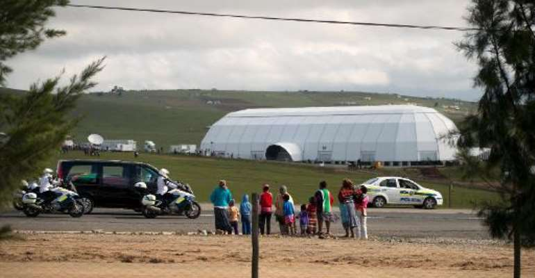 The hearse carrying the coffin of former South African president Nelson Mandela passes the dome funeral venue set up for tomorrow's funeral in Qunu, on December 14, 2013.  By Pedro Ugarte (AFP)