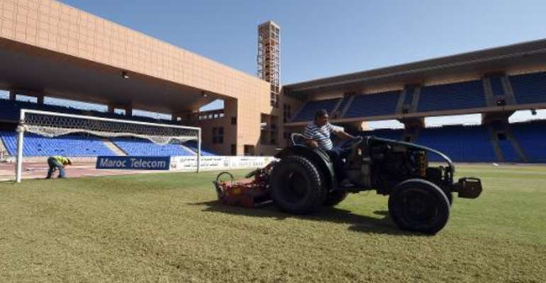 An employee cuts the grass on October 20, 2014 at the Marrakesh Stadium in the southern Moroccan city.  By Fadel Senna (AFP/File)
