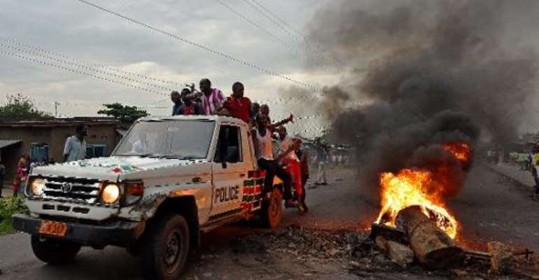 Protestors opposed to the Burundian president Pierre Nkurunziza's third term in office hitch a ride on a police vehicle past a burning barricade during a demonstration in the Cibitoke neighborhood of Bujumbura on May 19, 2015.  By Carl De Souza (AFP)