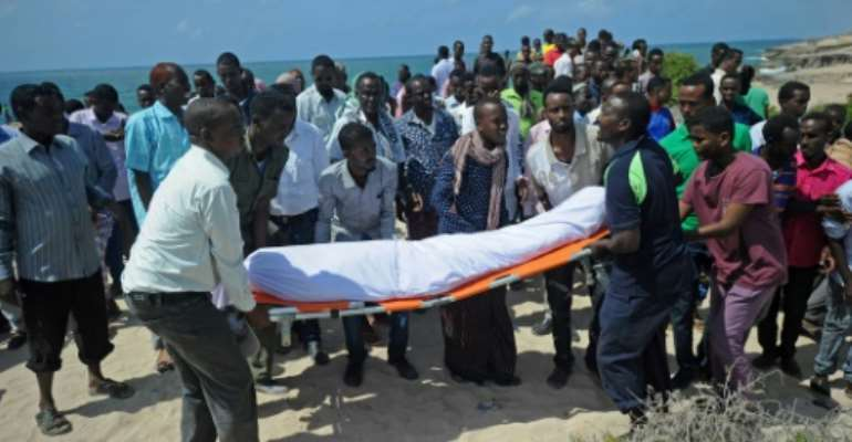 Relatives and fellow journalists pray as they stand next to the body of  journalist Abdulaziz Ali Haji during his 2016 funeral in Somalia, described by a watchdog group as the worst country for enabling impunity for deadly attacks on media.  By Mohamed ABDIWAHAB (AFP/File)