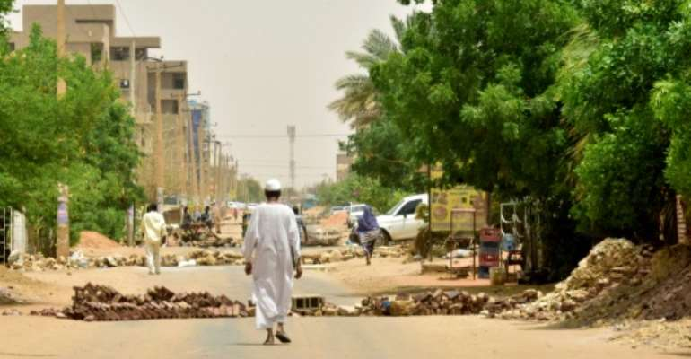 Residents walk past barricades in the Sudanese capital.  By - (AFP)
