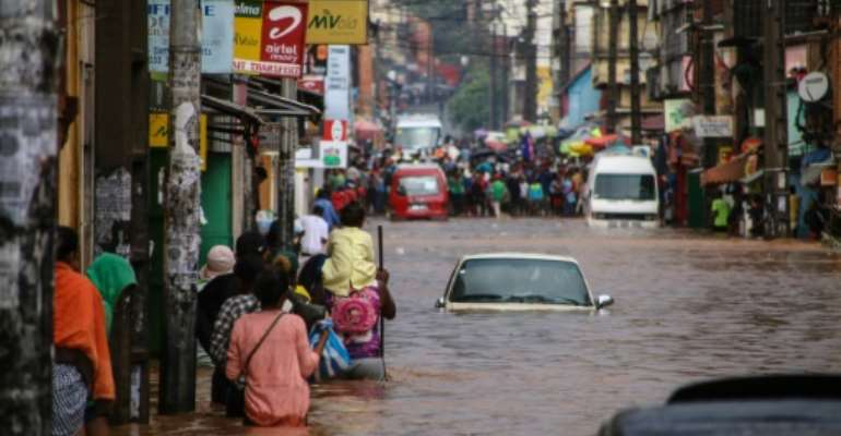 Residents walk through floodwaters past submerged vehicles on a road in the capital Antananarivo.  By MAMYRAEL (AFP/File)