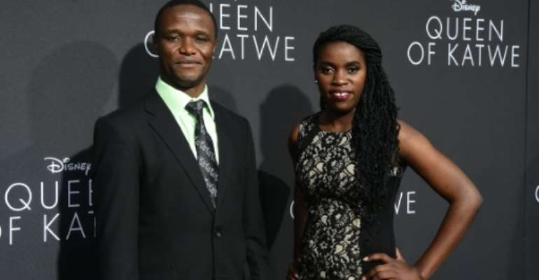 Robert Katende and Phiona Mutesi (R), whose life on which the story is based, pose on arrival for the premiere of Disney's