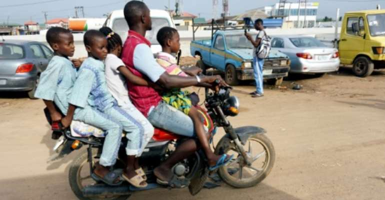 Room for one more? A traditional motorcycle taxi on Lagos roads -- overladen and not a crash helmet in sight.  By PIUS UTOMI EKPEI (AFP)
