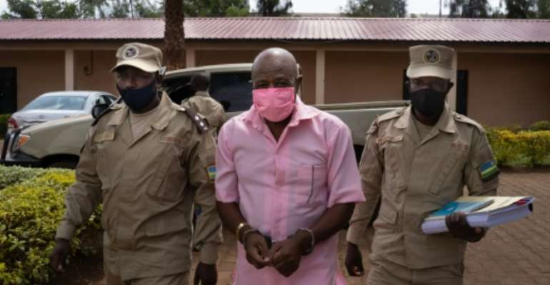 Rusesabagina in pink prison uniform, arriving at the Nyarugenge Court of Justice in Kigali last October.  By Simon Wohlfahrt (AFP/File)