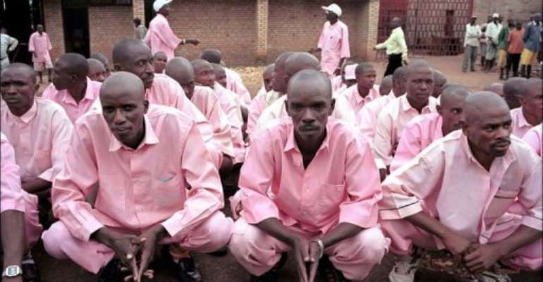 Prisoners in pink uniforms wait inside the prison of Gitarama to be transferred and attend a gacaca court session.  By Thomas Lohnes (AFP/DDP/File)