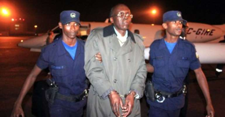 Rwandan ex-politician Leon Mugesera is escorted by policemen to a vehicle at Kigali airport on January 24, 2012.  By Steve Terrill (AFP/File)
