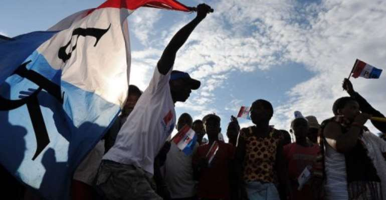 A man holds a party flag as supporters of the ruling Rwandan Patriotic Front (RPF) rally in Kigali on September 14, 2013.  By Tony Karumba (AFP/File)