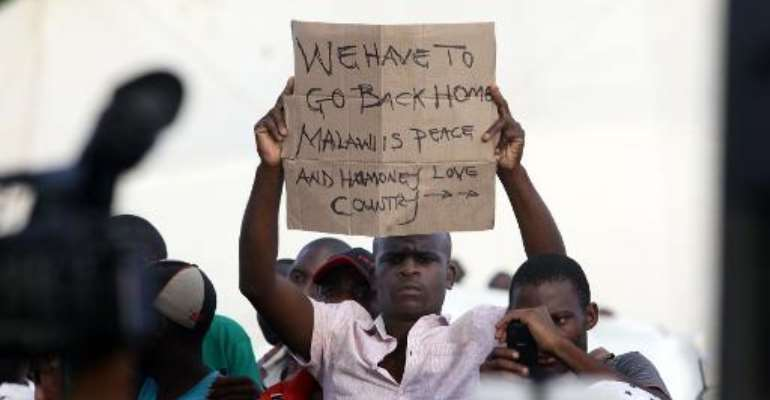 A foreign national shows a sign as South African President Jacob Zuma addresses a temporary refugee camp in Chatsworth, south of Durban on April 18, 2015 during a visit marked by hostile reaction.  By Rajesh Jantilal (AFP)