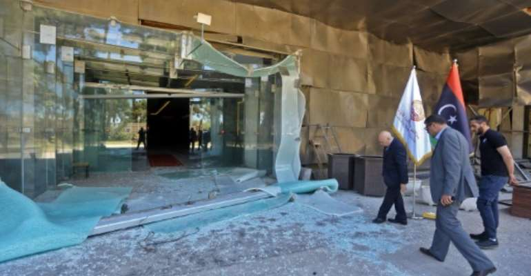 Sadeq al-Keheli (L), interim speaker for a faction of Libyan parliamentarians opposed to strongman Khalifa Haftar, inspects damage at a hotel serving as a HQ in Tripoli.  By Mahmud TURKIA (AFP)