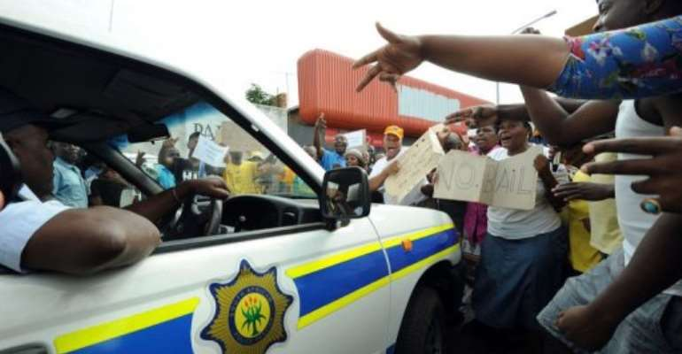 Protesters shout as a police car drives outside the Benoni court on March 8, 2013.  By Alexander Joe (AFP)