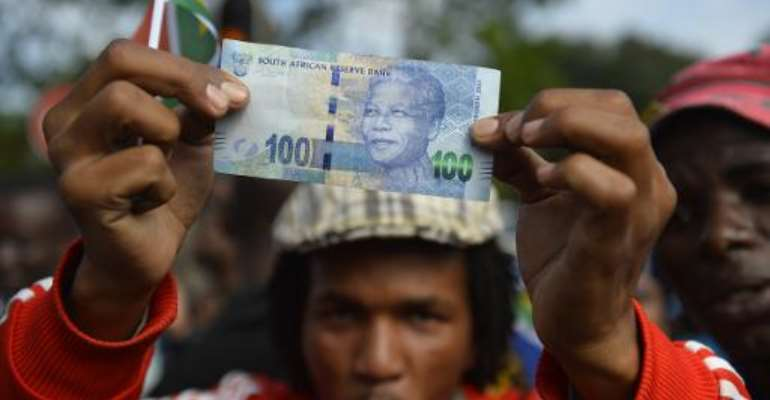 A man holds a 100 rand bill bearing the portrait of South African former president Nelson MandelaMandela as Mandela's funeral cortege drives through the streets in Pretoria on December 11, 2013.  By Odd Andersen (AFP/File)