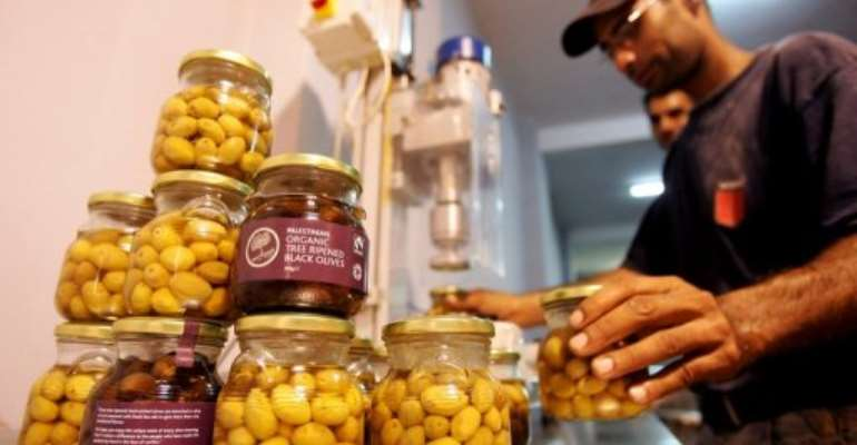 A Palestinian man organizes jars of olives grown in the West Bank.  By Saif Dahlah (AFP/File)
