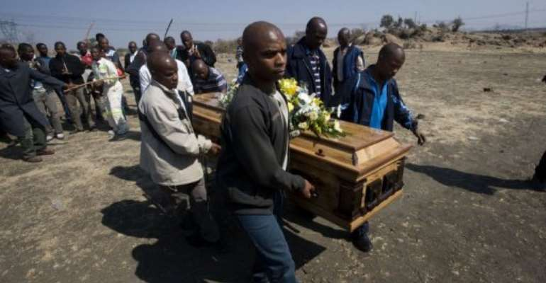 A group of men carry the body of a miner near the Lonmin mine in Marikana.  By Rodger Bosch (AFP)